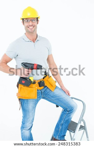 Portrait of confident worker holding drill machine on step ladder over white background - stock photo
