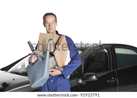 Portrait of confident worker with handful of mechanic stuff in front of car over white background - stock photo