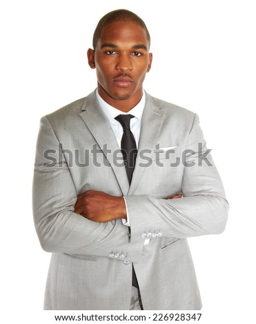 Portrait of confident young African American businessman standing arms folded over white background - stock photo