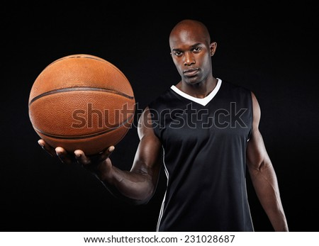 Portrait of confident young basketball player with a ball looking at camera against black background - stock photo