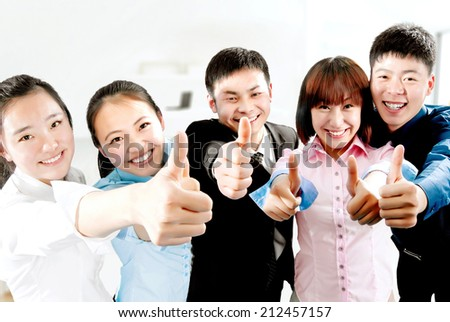 Portrait of confident young business people with thumbs up  - stock photo