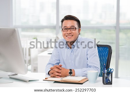Portrait of confident young businessman at his workplace - stock photo