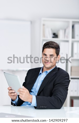 Portrait of confident young businessman holding digital tablet at desk in office - stock photo