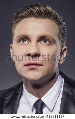 Portrait of confident young businessman in studio. Young businessman looking at camera with discrete smiling and proud expression. - stock photo