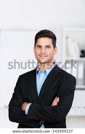 Portrait of confident young businessman with arms crossed in office - stock photo