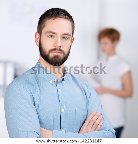 Portrait of confident young businessman with female coworker reading document in background at office - stock photo
