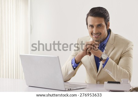Portrait of confident young businessman with laptop sitting at office desk - stock photo
