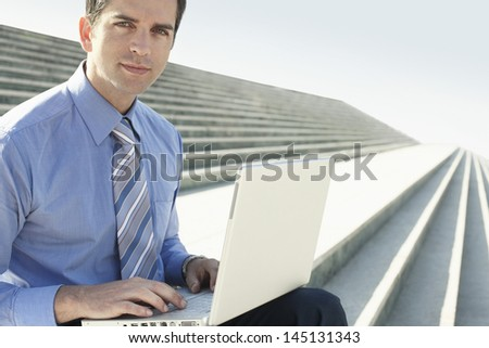 Portrait of confident young businessman with laptop sitting on marble staircase against clear sky - stock photo