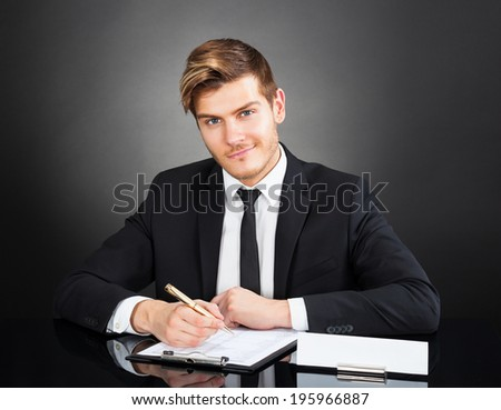 Portrait of confident young businessman working at desk against black background - stock photo