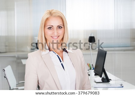 Portrait of confident young businesswoman smiling in office - stock photo