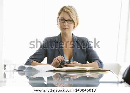 Portrait of confident young businesswoman with cell phone and paperwork in conference room - stock photo