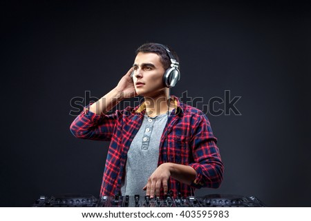 Portrait of confident young DJ with stylish haircut and headphones on head mixing music on mixer on dark background.  - stock photo