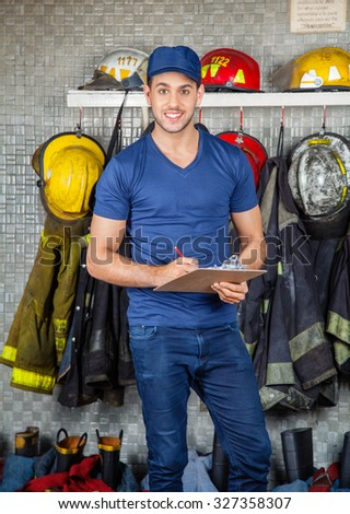 Portrait of confident young firefighter holding clipboard at fire station - stock photo