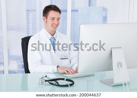 Portrait of confident young male doctor using computer at desk in clinic - stock photo
