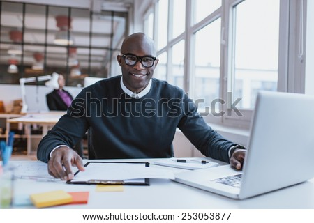 Portrait of confident young man at his desk with laptop doing paperwork. Happy african man looking at camera while at work. - stock photo