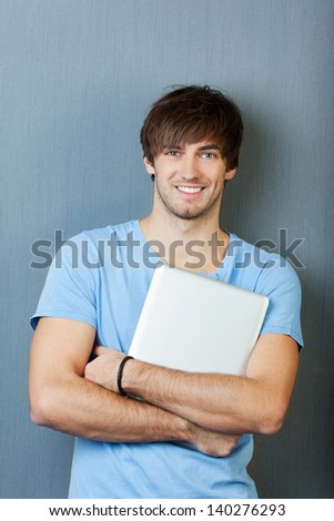 Portrait of confident young man laptop standing against blue wall - stock photo