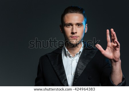 Portrait of confident young man magician with raised hand over grey background - stock photo