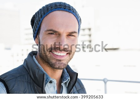 Portrait of confident young man wearing beanie hat and jacket - stock photo