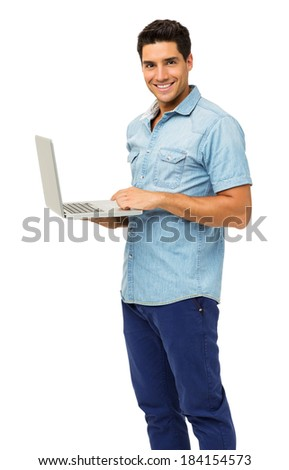 Portrait of confident young man with laptop standing over white background. Vertical shot. - stock photo