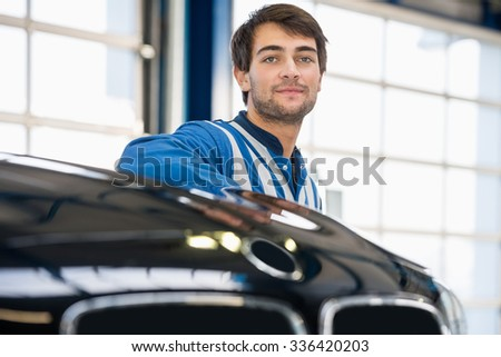 Portrait of confident young mechanic standing by car in garage - stock photo