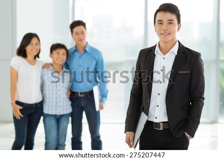 Portrait of confident young real estate broker and happy family in the background - stock photo