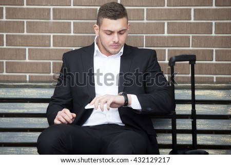 Portrait of confident young travelling business man looking at watch with serious facial expression outdoors. Successful attractive caucasian man sitting on the bench with his luggage - stock photo