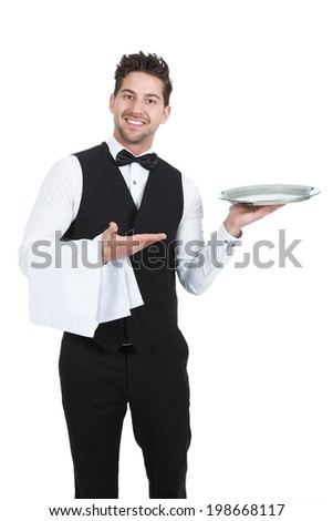 Portrait of confident young waiter with napkin and serving tray standing isolated over white background - stock photo