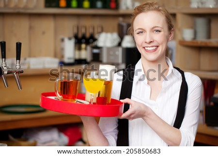 Portrait of confident young waitress carrying tray with coffee; juice and beer in restaurant - stock photo