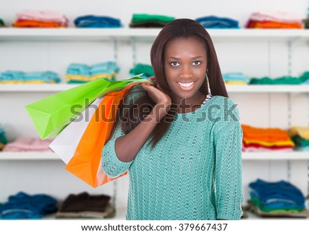 Portrait of confident young woman carrying shopping bags in store - stock photo