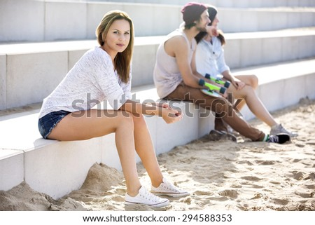 Portrait of confident young woman sitting on steps with skateboarders in background at beach - stock photo