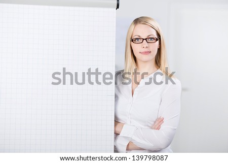 Portrait of confident young woman standing by flip chart in office - stock photo