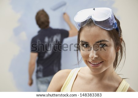 Portrait of confident young woman wearing protective glasses with man painting wall at home - stock photo