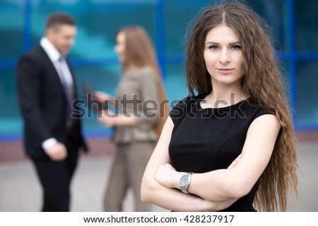 Portrait of confident young woman with crossed arms and serious facial expression looking at camera outdoors. Successful beautiful woman posing on the street with businesspeople on the background - stock photo