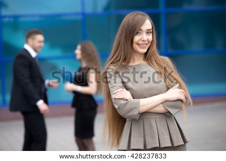 Portrait of confident young woman with crossed arms smiling at camera outdoors. Happy beautiful friendly caucasian woman posing on the street in summer with businesspeople on the background - stock photo