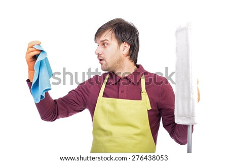 Portrait of confused young man with apron and cleaning equipment over white background - stock photo