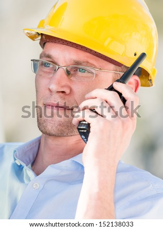 Portrait of construction manager using walkie-talkie - stock photo