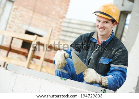 Portrait of construction mason worker bricklayer installing brick with trowel putty knife outdoors - stock photo
