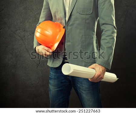 Portrait of construction master holding yellow helmet and blueprint in hands. - stock photo