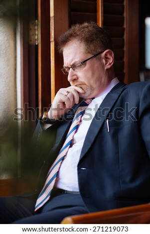 Portrait of contemplating mature businessman in glasses - stock photo