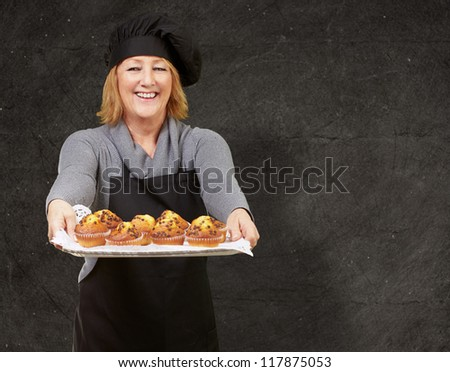 portrait of cook woman showing a homemade muffins tray against a grunge wall - stock photo