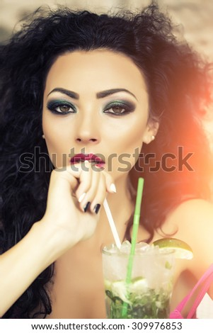 Portrait of cool beautiful brunette woman with curly hair and bright makeup with alcoholic mojito cocktail from mint soda light rum ice cubes and lime with straw, vertical picture - stock photo