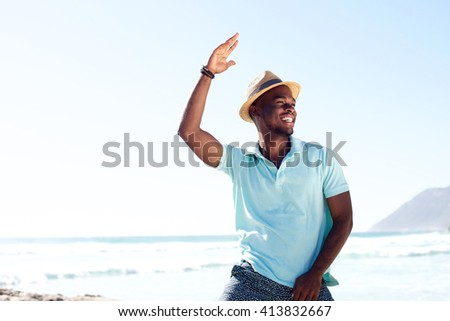 Portrait of cool young african man dancing at the beach on summer day - stock photo