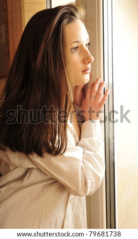 Portrait of cosy young girl standing near a window at home - stock photo