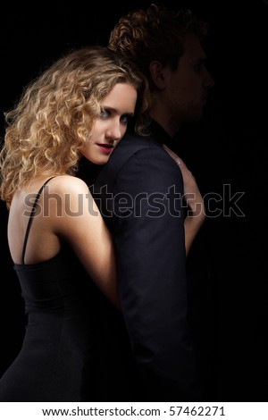 portrait of couple - blonde girl embraces man from behind. man's face in dark - stock photo