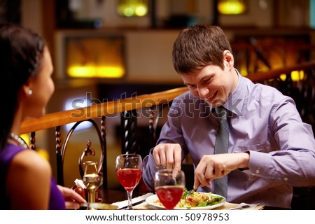 Portrait of couple eating dish in the restaurant - stock photo