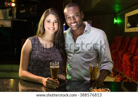 Portrait of couple having beer at bar counter in bar - stock photo