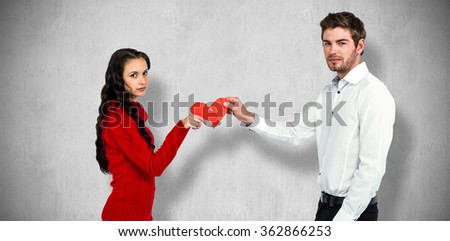 Portrait of couple holding red cracked heart shape against white and grey background - stock photo
