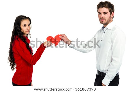 Portrait of couple holding red cracked heart shape over white background - stock photo