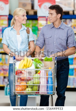 Portrait of couple in the shop with cart full of food. Concept of consumerism and healthy food - stock photo