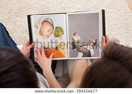Portrait Of Couple Looking At Photo Album - stock photo